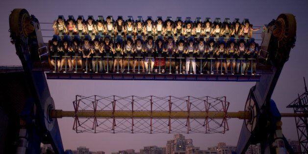 SHENZHEN, CHINA - SEPTEMBER 29: Chinese tourists ride a carnival ride at dusk at Happy Valley Theme park...