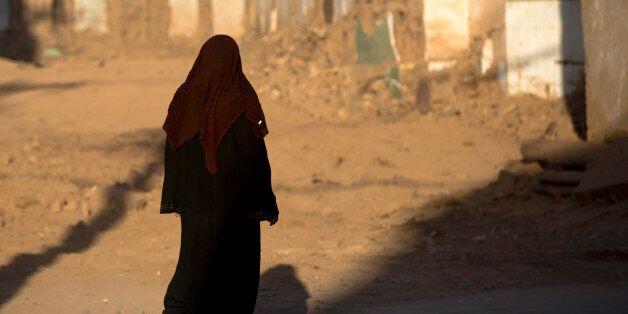 KASHGAR, CHINA - SEPTEMBER 21: Woman passing by demolished houses, Old town of Kashgar, Xinjiang Uyghur...