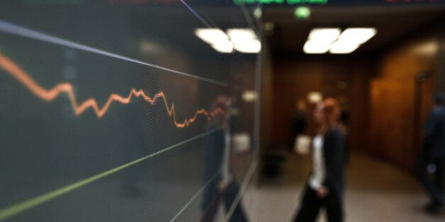 An employee passes an electronic index curve displaying current share prices in the Hellenic Exchanges...