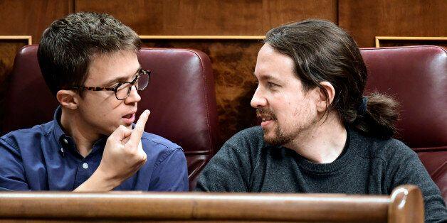 Podemos' leader Pablo Iglesias (R) looks at Podemos' representative Inigo Errejon at the Spanish Congress...