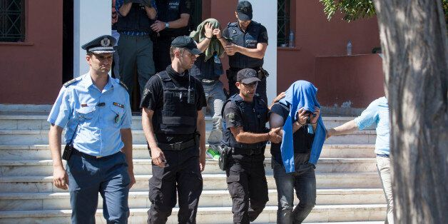 A Greek police officer escorts a Turkish officer who fled to Greece by helicopter after last week's failed...