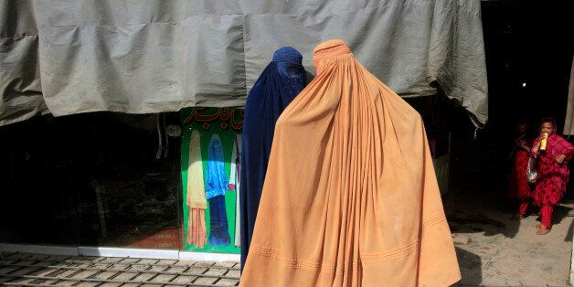 Afghan women, clad in burqas, stand outside a shop at a market in Peshawar, Pakistan June 29, 2016. REUTERS/Fayaz