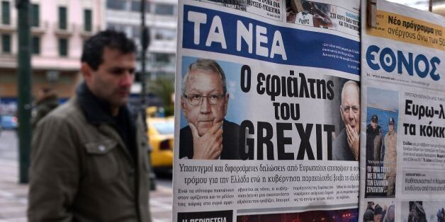 A man looks at newspapers bearing headlines reading 'The nightmare of Grexit' on January 31, 2017. /...