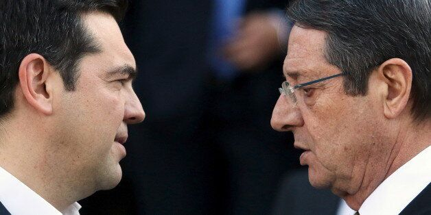 Cypriot President Nicos Anastasiades (R) and Greek Prime Minister Alexis Tsipras talk outside the Presidential...