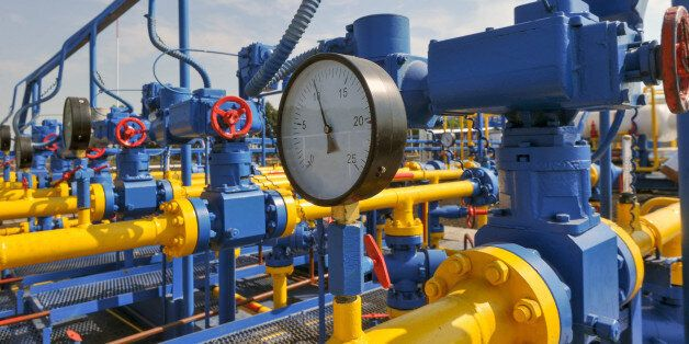 Pressure meter and red faucet with steel yellow pipe in natural gas treatment plant in bright sunny summer