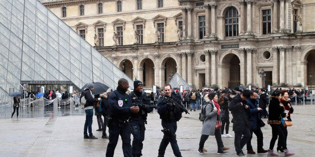Police officers patrol in front of the Louvre Pyramid in Paris on February 4, 2017 a day after a machete-wielding...