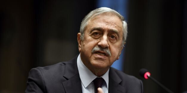 Turkish Cypriot leader Mustafa Akinci gestures as he speaks during a press conference on UN-sponsored...