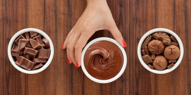 Three bowls with varieties of chocolate foods and woman's hand holding the middle one