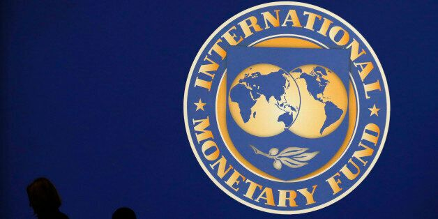Visitors are silhouetted against the logo of the International Monetary Fund at the main venue for the...