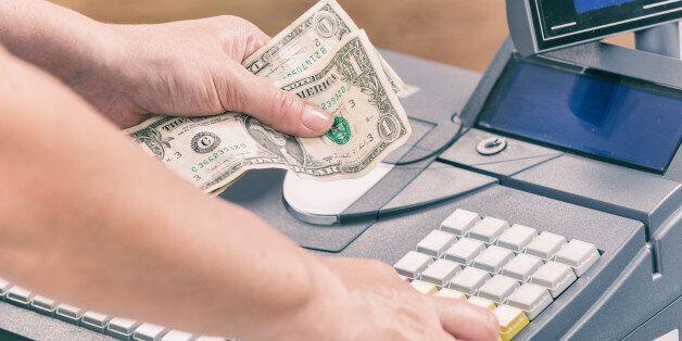 Cashier holdnig banknotes and using cash register at