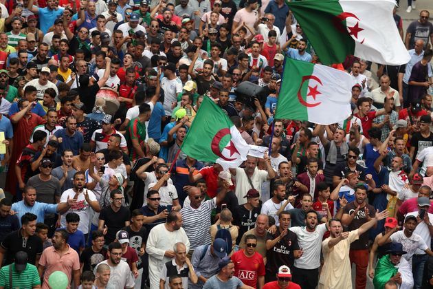 Demonstrators shout slogans during a protest to reject the Algerian election announcement for December,...