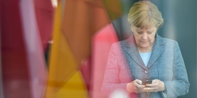 German chancellor Angela Merkel looks at her smartphone while waiting at the chancellery for the arrival...