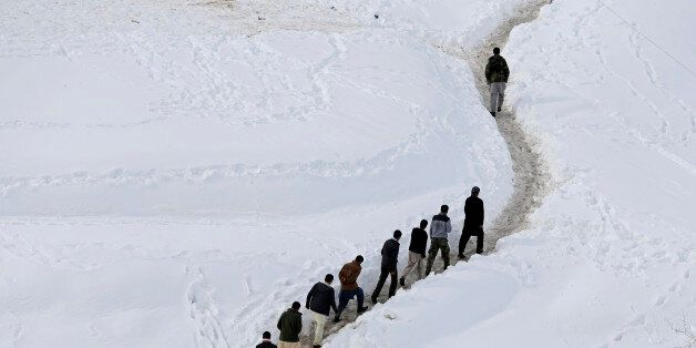 Afghan survivors of an avalanche walk in the Abdullah Khil village of the Dara district of Panjshir province...