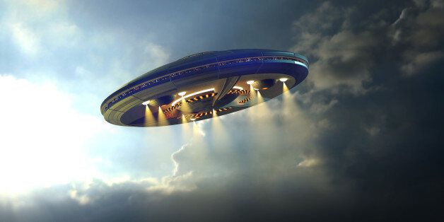 Alien UFO saucer flying on a clouds background above