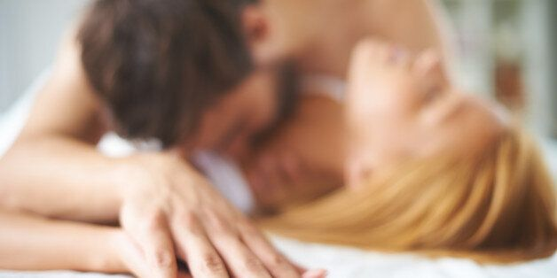 Hands of female and male lying on bed