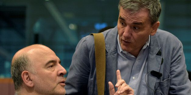 European Economic and Financial Affairs Commissioner Pierre Moscovici (L) chats with Greece's finance...