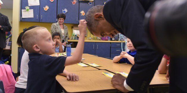 US President Barack Obama offers leans over for a boy to feel his hair during a visit to an elementary...