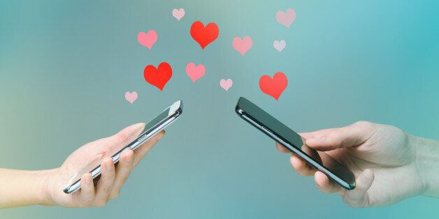 Young man and woman's hands holding smart phones with hearts floating