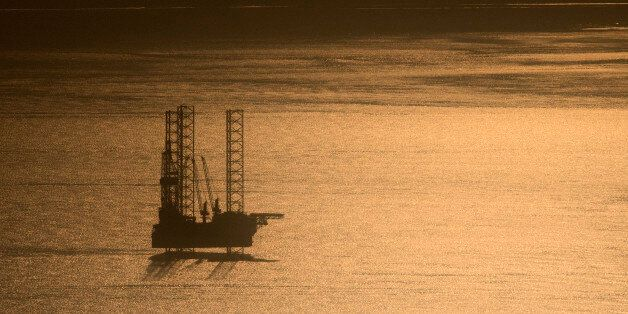 A picture taken on January 13, 2017 shows an off-shore oil rig, off the coast of Port-Gentil at sunrise....