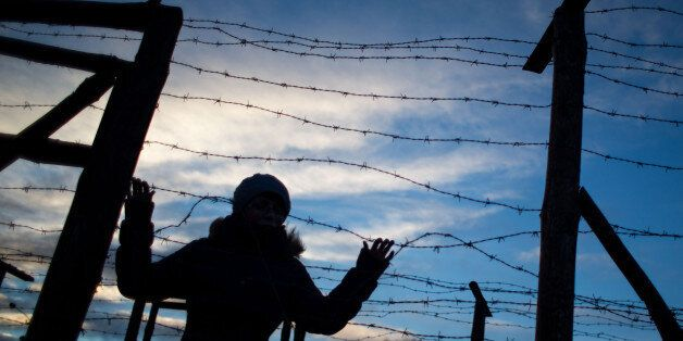 A woman stands behind remains of the border fences from the former 'Iron curtain' between Slovakia and...
