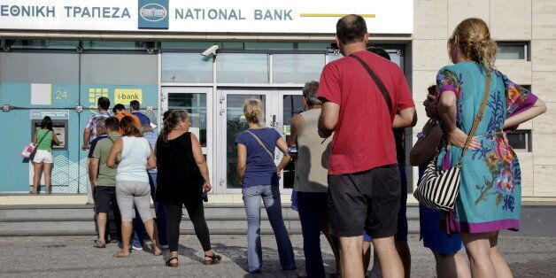 People line up to withdraw cash from an automated teller machine (ATM) outside a National Bank branch...