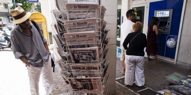 People withdraw cash from an ATM machine in downtown Athens on July 7, 2015. Eurozone leaders will hold...