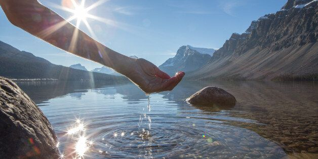 Human hand cupped to catch the fresh water from the lake, sunlight from sunset passing through the transparence...