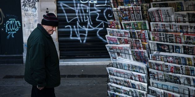 A Greek man looks at newspaper headlines at a kiosk in Athens on January 29, 2017.Two historic Greek...