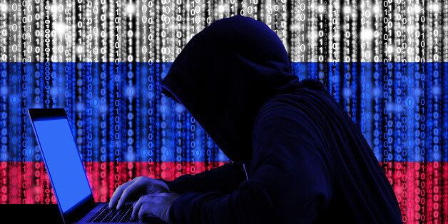 Hacker in a dark hoody sitting in front of a notebook with digital russian flag and binary streams background...