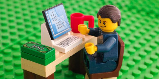 Tambov, Russian Federation - March 24, 2015: Lego businessman sits at his working table with computer,...