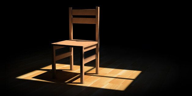 Chair on a dark room illuminated only by a light coming from a