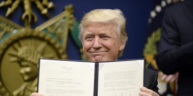 U.S. President Donald Trump holds up signed executive orders in the Hall of Heroes at the Department...