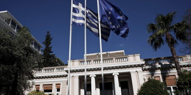 A Greek national flag and a European Union flag flutter outside the Maximos mansion as a government council...