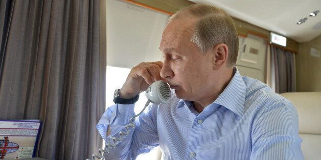 Russian President Vladimir Putin speaks on the phone while inspecting the area, damaged by wildfires...