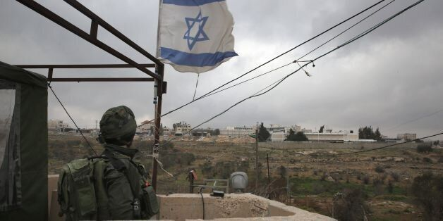 This photo taken on January 25, 2017 shows an Israeli soldier standing guard in a monitoring cabin in...