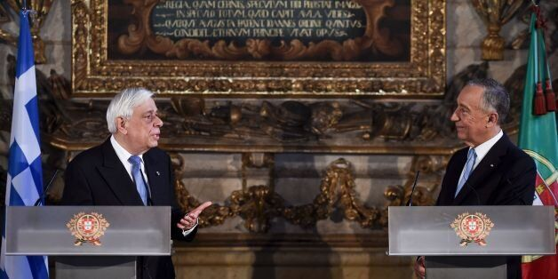 Greek President Prokopios Pavlopoulos (L) and Portuguese President Marcelo Rebelo de Sousa (R) hold a...