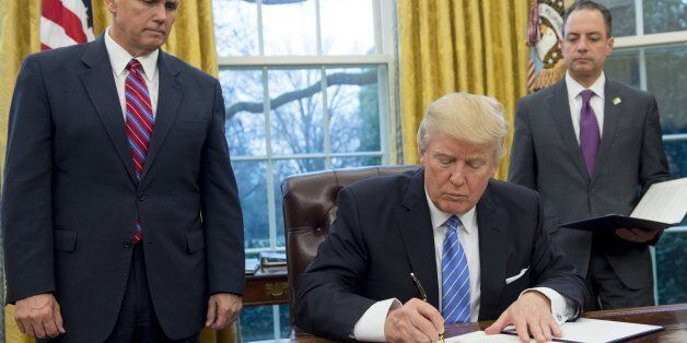 US President Donald Trump signs an executive order withdrawing the US from the Trans-Pacific Partnership...