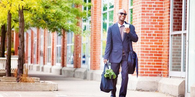 Mature businessman walking  home with phone and groceries, smiling.