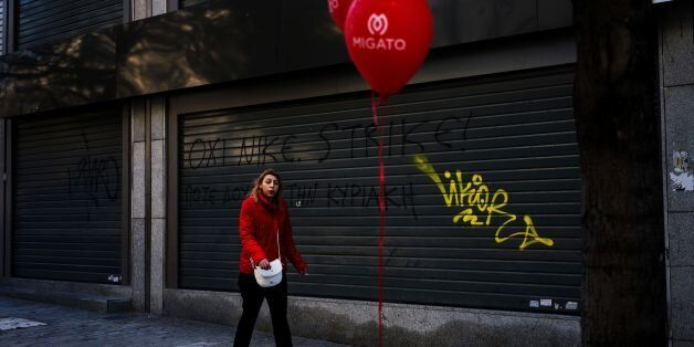 A woman walks in front of a closed shop with a graffiti tag reading 'strike' in the center of Athens...