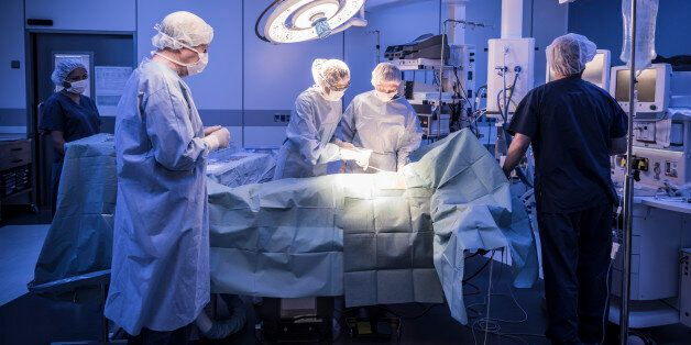 Four doctors in hospital operating room with patient lying on operating table. Surgical lights shining...