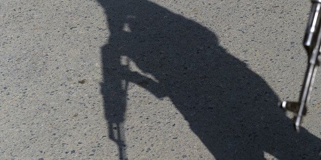 The shadow of an Afghan policeman falls onto the ground as he keeps watch near the largest US military...
