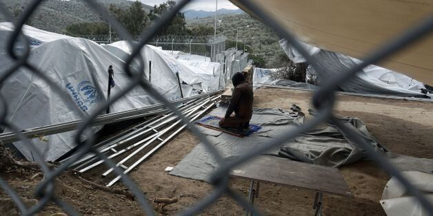A man prays in the Moria migrant camp on the Greek island of Lesbos on December 30, 2016.There are over...