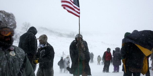 A man holds an American flag while marching with veterans and activists outside the Oceti Sakowin camp
