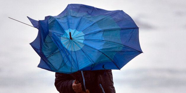 A man battles with his broken umbrella in heavy wind during stormy weather close to the town of Baiona, northwestern Spain, on February 3, 2017.  / AFP / MIGUEL RIOPA        (Photo credit should read MIGUEL RIOPA/AFP/Getty Images)