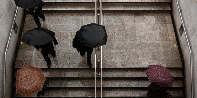 Commuters carry umbrellas as they make their way in and out of Syntagma metro station in Athens January...