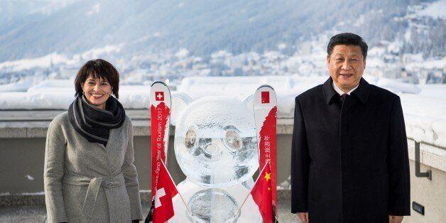 Swiss Federal President Doris Leuthard (L) and China's President Xi Jinping (R) pose next to a panda...