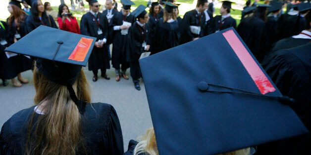 Graduating students wear red tape on their caps in solidarity with victims of sexual abuse during the...