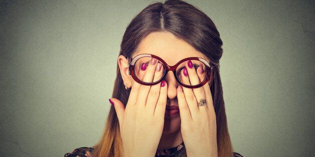Closeup portrait young woman in glasses covering face eyes using her both hands isolated on gray wall