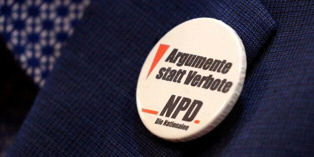 A member of the Nationaldemokratische Partei Deutschlands (NPD) presents a buton with the