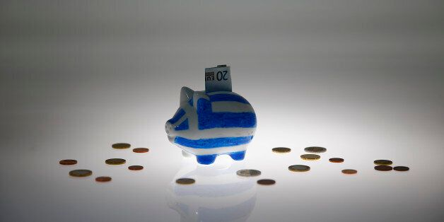 A piggybank painted in the colours of the Greek flag with a 20 euro banknote in it's slot, stands amongst...